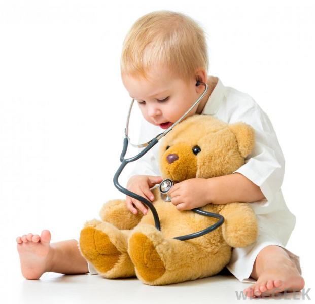 Child with stethescope and teddy bear